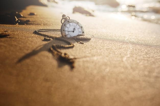 Montre de poche vintage sur la plage de sable doré