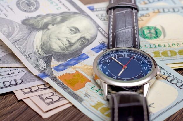 La montre repose sur des dollars. il est temps de gagner de l'argent. le temps, c'est de l'argent