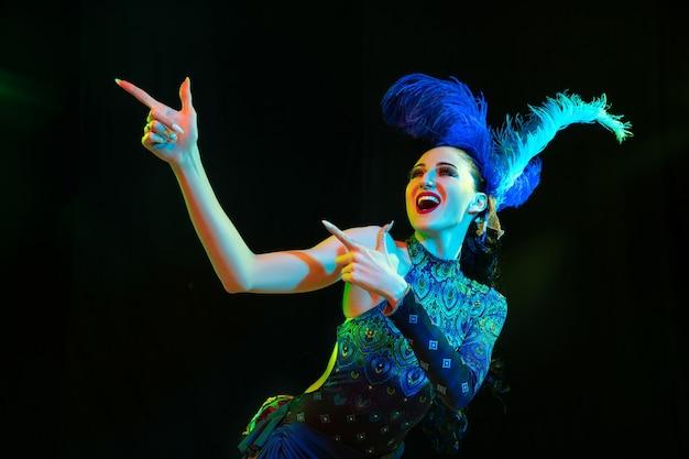 Montrer du doigt. belle jeune femme en carnaval, costume de mascarade élégant avec des plumes sur fond noir à la lumière du néon. copyspace pour l'annonce. fête des fêtes, danse, mode. temps de fête, fête.