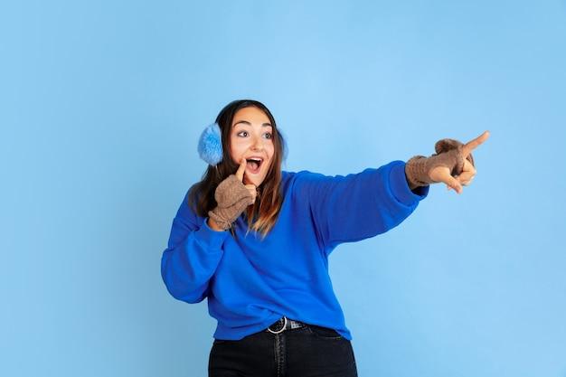 Montrer du doigt. portrait de femme caucasienne sur fond bleu studio. beau modèle féminin dans des vêtements chauds. concept d'émotions humaines, expression faciale, ventes, publicité. humeur hivernale, période de noël, vacances.