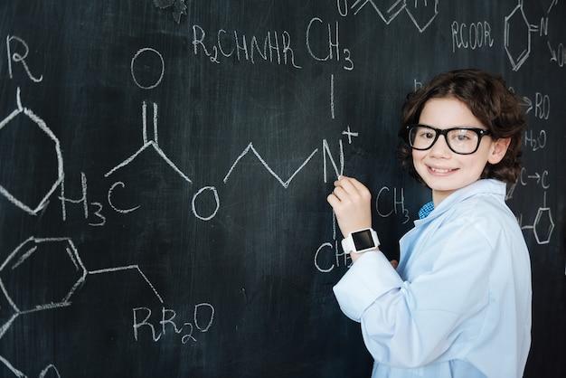 Montrer mes capacités. heureux élève doué intelligent debout dans le laboratoire tout en profitant d'un cours de chimie et en prenant des notes sur le tableau noir