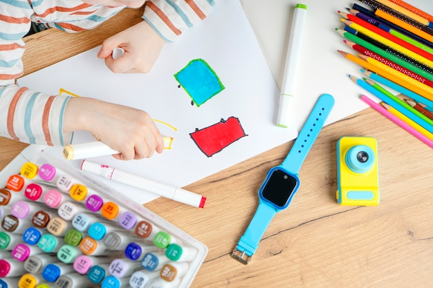 Montres bébé intelligentes avec écoutes téléphoniques, surveillance à distance et traceur gps posés sur la table près de l'enfant à la maternelle. le garçon dessine dans l'album avec des feutres. voir ci-dessus.