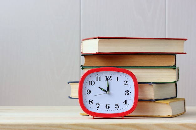 Montres et livres. pile de manuels scolaires sur la table.