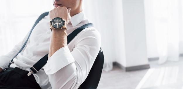 Montres de luxe de couleur dorée sur la main du jeune homme élégant.