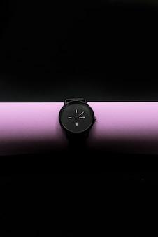 Montres noires sur tube brillant. fond abstrait noir foncé, un objet. horizontal