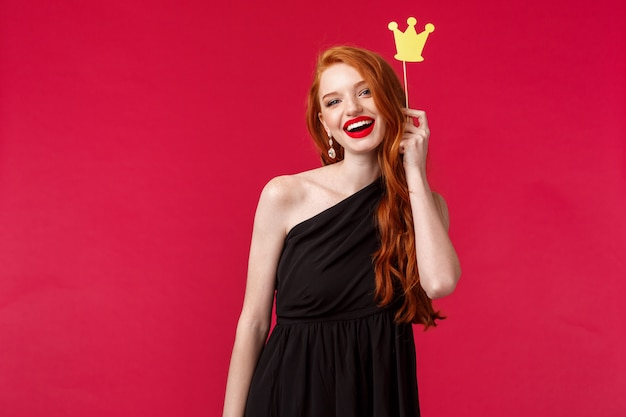 Montrez-leur qui est la reine. adorable femme rousse caucasienne en robe noire luxueuse, rouge à lèvres, tenant la couronne sur le bâton et souriant, s'amusant avec les copines la nuit, sur un mur rouge