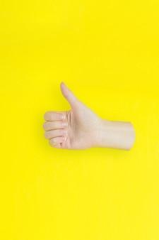 Montrez à la main comme ou bon signe de réussite et agréable sur fond jaune.
