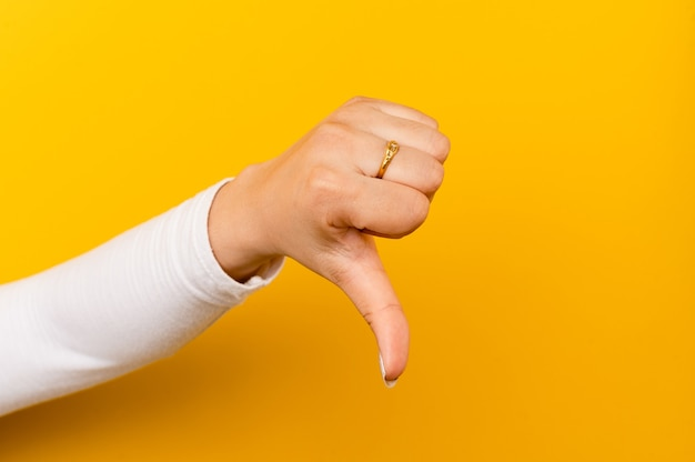 Montrez que vous n'aimez pas les pouces vers le haut sur un fond de papier jaune désapprouvant et désapprouvant les gestes en désaccord avec ce que vous n'aimez pas