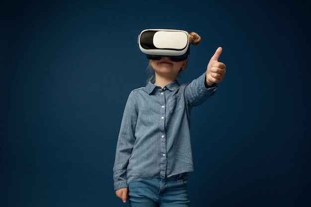Montrez votre esprit. petite fille ou enfant en jeans et chemise avec des lunettes de casque de réalité virtuelle isolés sur fond bleu studio. concept de technologie de pointe, jeux vidéo, innovation.
