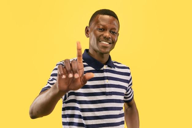 Montrez-vous du doigt. jeune homme afro-américain isolé sur fond de studio jaune, expression faciale. beau portrait d'homme demi-longueur. concept d'émotions humaines, expression faciale.