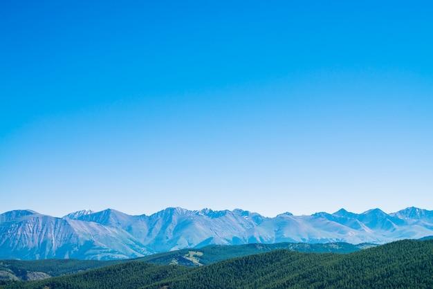 Monts géants et glaciers au-dessus des collines avec forêt. crête enneigée sous un ciel bleu clair. sommet de neige dans les hautes terres. pergélisol, froid permanent. incroyable paysage de montagne minimaliste atmosphérique.