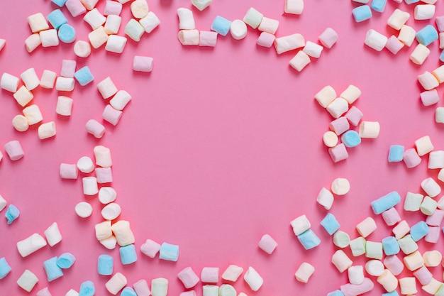 Monture faite de bonbons guimauve sucrés blancs et roses avec espace de copie sur fond rose.