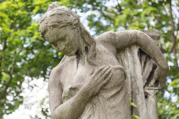 Monument de la jeune femme sur une tombe dans un cimetière