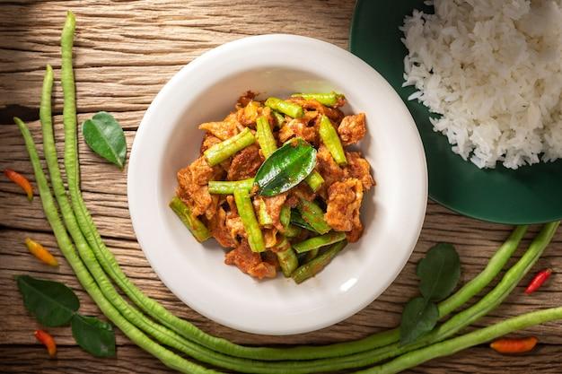 Moo pad prik gaeng, cuisine thaïlandaise, porc sauté avec pâte de curry rouge, feuilles de bergamote et haricots yardlong à côté de riz coulé sur fond de texture de bois naturel rustique, vue de dessus