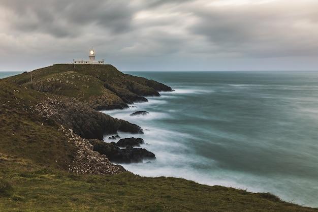 Moody seascape avec phare sur les falaises
