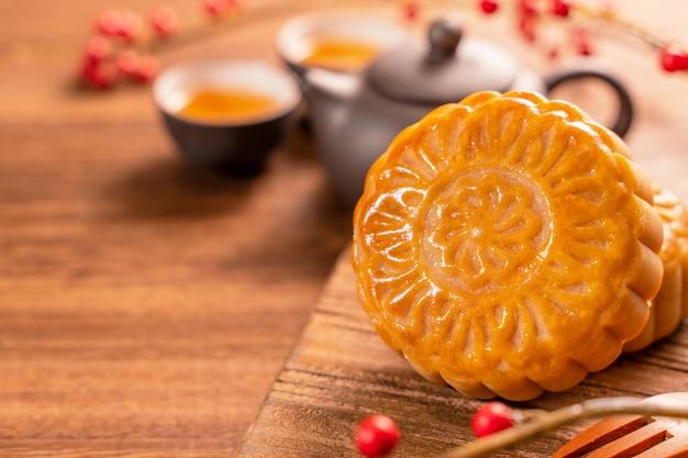 Moon cake mooncake table setting - pâtisserie traditionnelle chinoise de forme ronde avec des tasses à thé sur fond de bois, concept de festival de la mi-automne, gros plan