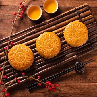 Mooncake mooncake table setting - pâtisserie traditionnelle chinoise avec des tasses à thé sur fond de bois, concept de festival de la mi-automne, vue de dessus, mise à plat