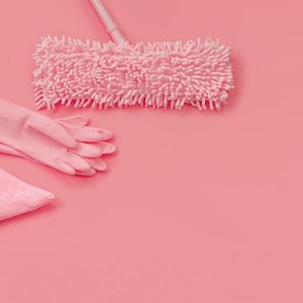 Mop, gants de chiffon et de caoutchouc-rose sur fond rose pour le nettoyage de printemps