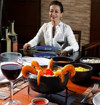 Moqueca brésilienne (muqueca) - crevettes mijotées dans de la crème de noix de coco et de l'huile de palme servies avec un ragoût de poisson d'eau salée