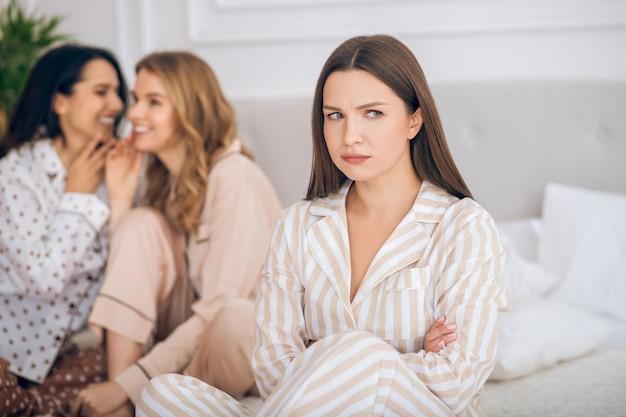 Moquerie. deux filles assises sur un lit et parlant de leur amie derrière son dos