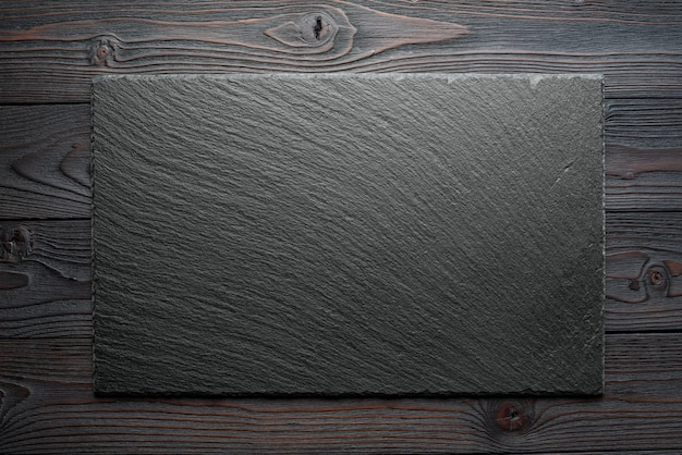 Morceau d'ardoise vide sur une table en bois, composition horizontale