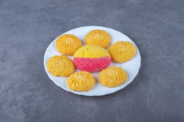 Un morceau de biscuit et de biscuit en forme de pêche sur une assiette sur une table en marbre.