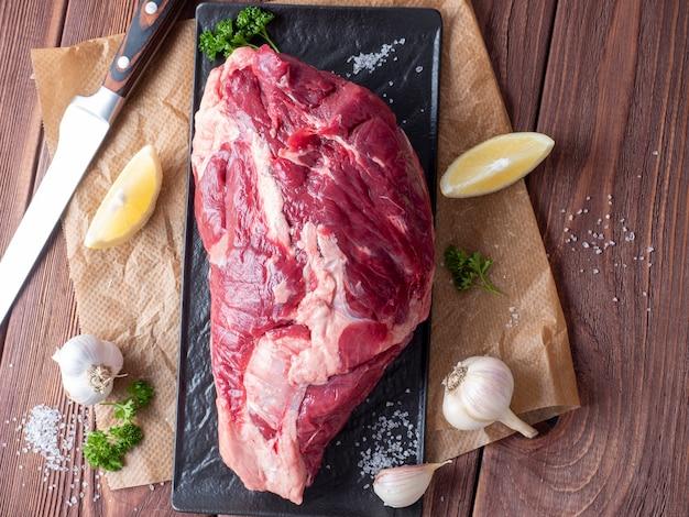 Un morceau de bœuf cru frais repose sur du parchemin entouré d'épices, d'herbes et de légumes. le couteau se trouve à proximité. vue de dessus, pose à plat. composition alimentaire