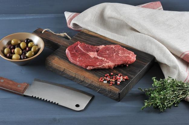 Morceau de bœuf cru sur une planche de bois, un couteau pour la viande, les olives et le thym