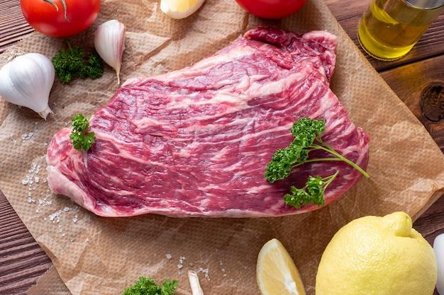 Un morceau de bœuf marbré repose sur du parchemin entouré d'herbes, d'ail et de sel. vue de dessus, mise à plat. composition alimentaire