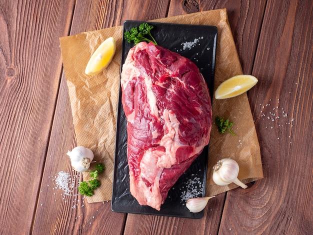 Un morceau de bœuf marbré repose sur du parchemin entouré d'herbes, d'ail, de sel. vue de dessus, mise à plat. composition des aliments