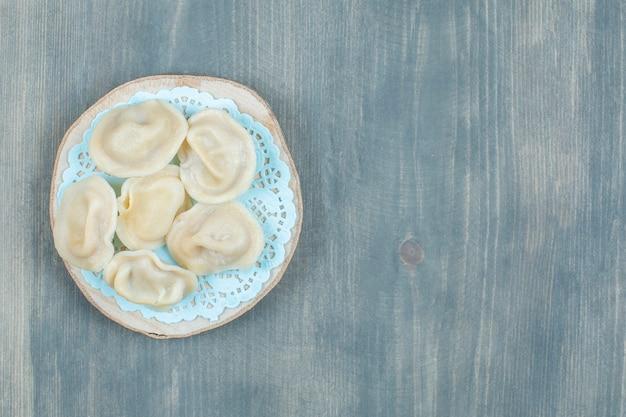 Morceau en bois de boulettes de viande bouillie sur une surface en bois.
