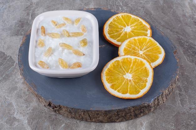 Un morceau de bouillie d'avoine saine en bois avec des raisins secs et des tranches de fruits orange.