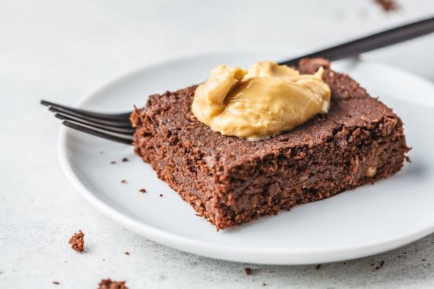 Morceau de brownie au chocolat végétalien avec du beurre de cacahuète sur une plaque blanche.