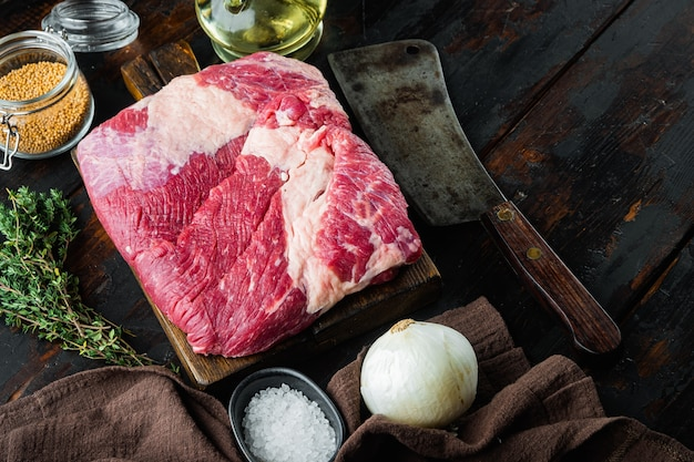 Morceau brut de poitrine de bœuf en marbre, avec des ingrédients pour fumer faisant du barbecue, du pastrami, du remède, sur une vieille table en bois foncé