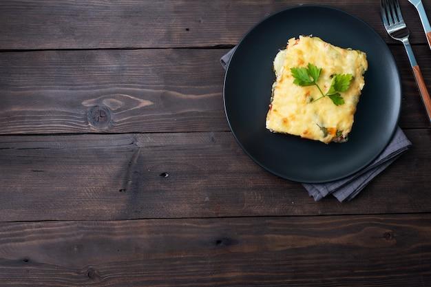 Morceau de casserole sur une assiette de pommes de terre et légumes avec du fromage. fond en bois foncé.