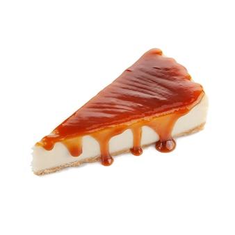 Un morceau de cheesecake classique avec une garniture au caramel. fond blanc. isoler. fermer.