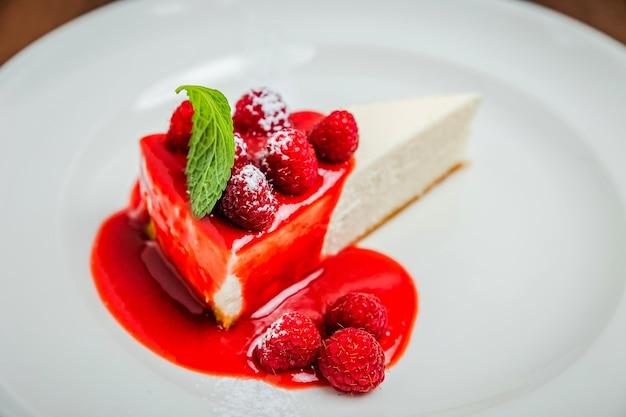 Un morceau de cheesecake new york classique, garniture de sirop de framboise, garni de petits fruits frais et de menthe