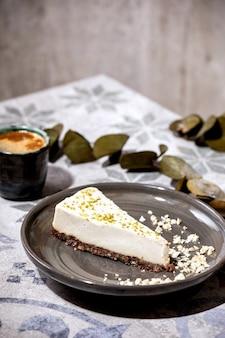 Morceau de cheesecake végétalien cru, sans gluten sans cuisson, décoré de zeste de citron vert et de noix de cajou sur assiette