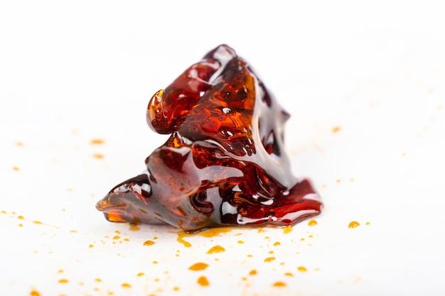 Un morceau de concentré de cire de cannabis ambre foncé en gros plan sur du papier blanc.