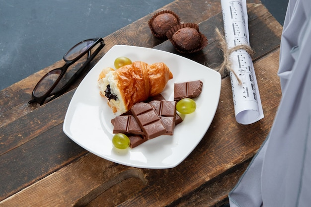 Morceau de croissant et barre de chocolat dans une assiette blanche sur la planche de bois
