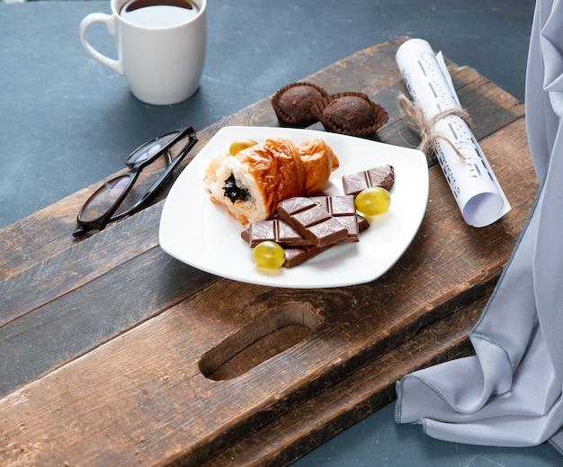 Morceau de croissant et barre de chocolat dans une assiette blanche avec une tasse de boisson