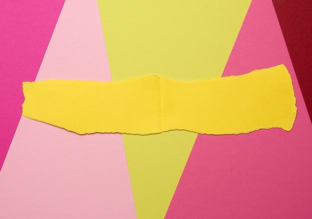 Morceau déchiré de papier jaune sur un espace coloré, toile de fond abstrait