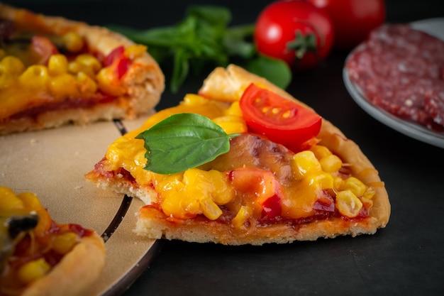 Morceau de délicieuse pizza italienne mordue sur fond sombre plat national authentique