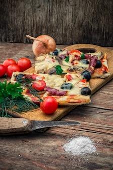 Morceau de délicieuse pizza à la viande avec du bacon et des olives sur le fond des légumes.