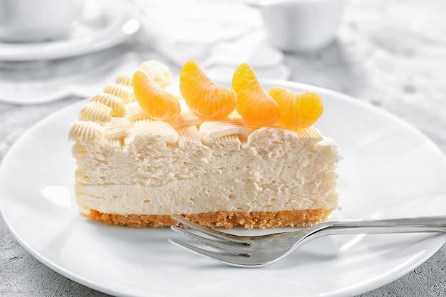 Morceau de délicieux cheesecake à la mandarine sur plaque blanche