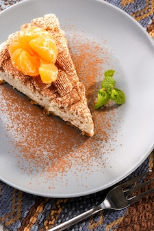 Morceau de délicieux cheesecake à la mandarine sur plaque grise
