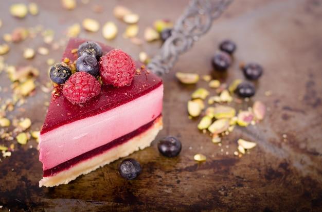 Morceau de délicieux gâteau aux framboises avec framboises fraîches, myrtilles, groseilles et pistaches à la pelle