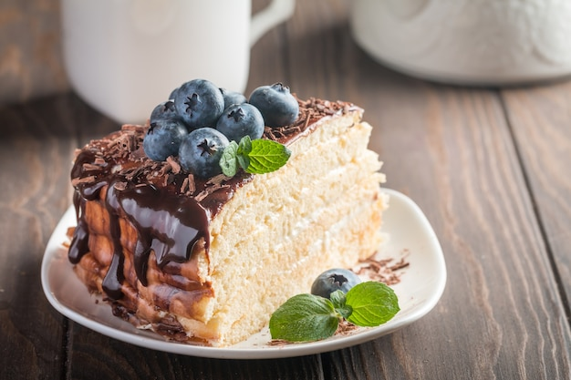 Morceau de délicieux gâteau éponge avec crème et chocolat sur plaque