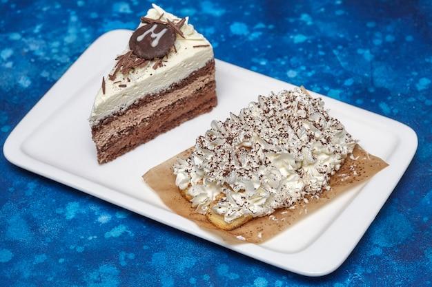 Morceau de délicieux gâteau mousse avec trois différents types de chocolat sur plaque blanche