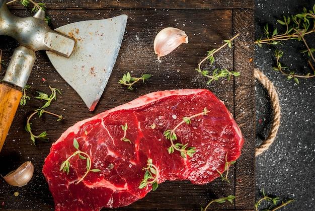Un morceau de filet de boeuf, avec une hache pour couper la viande sur le bois